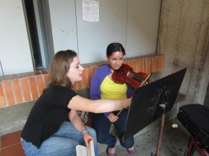 Sistema Fellow Julie Davis coaches a young violinist